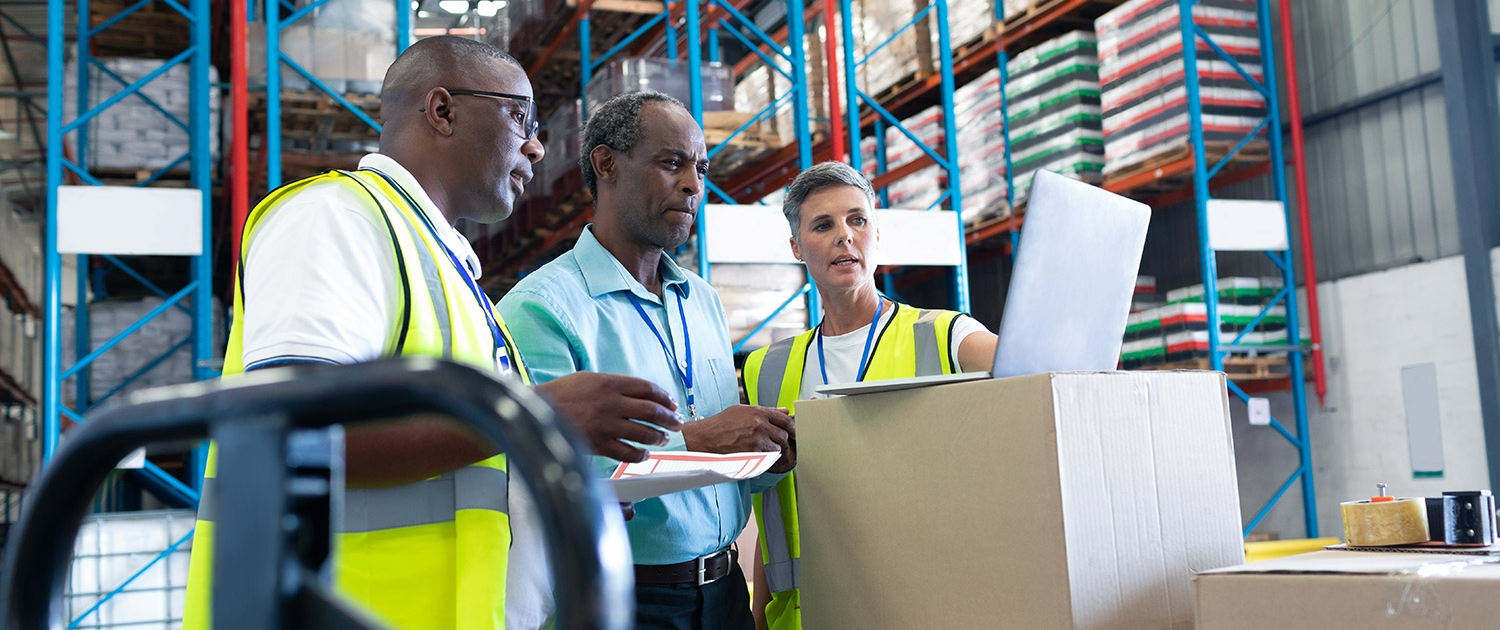 Side view of mature diverse warehouse staffs discussing over laptop in warehouse